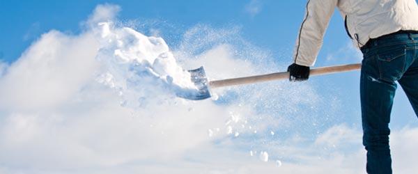 Mann der schwungvoll Schnee schaufelt